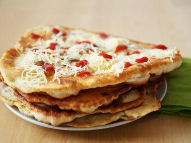 Langoše se zakysanou smetanou sypané sýrem
