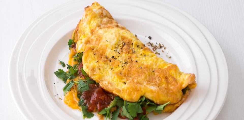 Austrálská snídaně  vaječná omeleta s rajčaty, sýrem a koriandrem ...